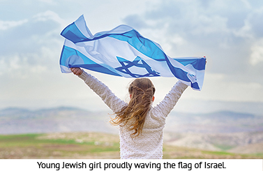 Young Jewish girl proudly waving the flag of Israel.